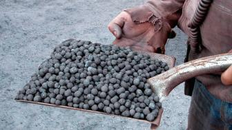 Two hands holding scoop end of shovel filled with grey round pellets