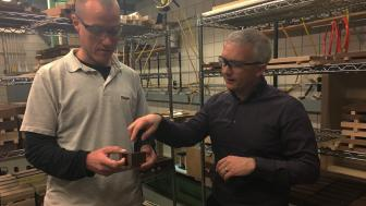 Two men looking at piece of dark wood in mechanical testing lab.