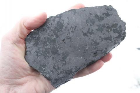 A hand is holding a larger-than-fist-sized grey, polished rock.