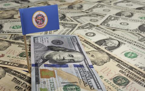 U.S. paper currency scattered with a state of Minnesota flag flying above.