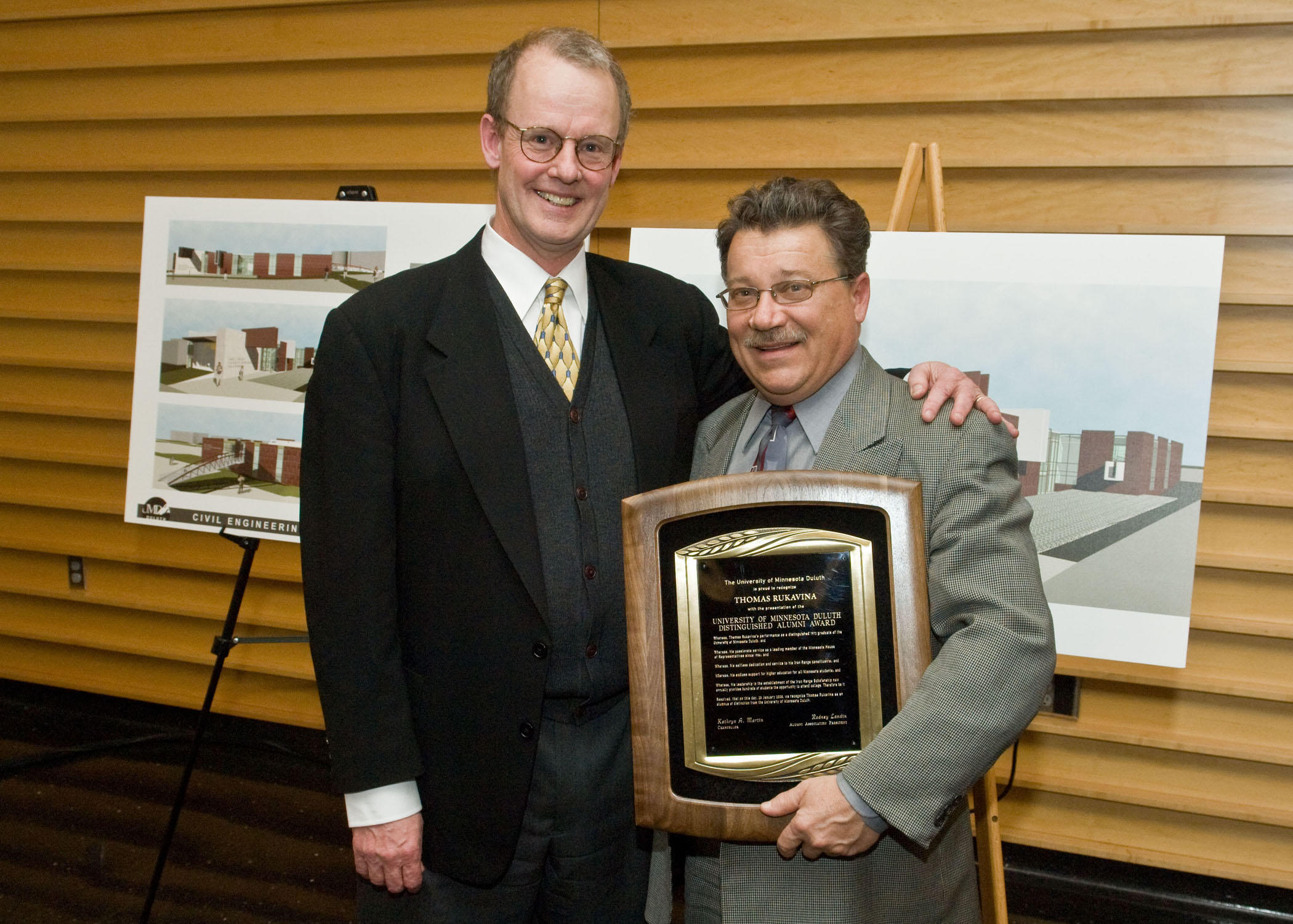 Two men pose for camera. Man on right holds a plaque.